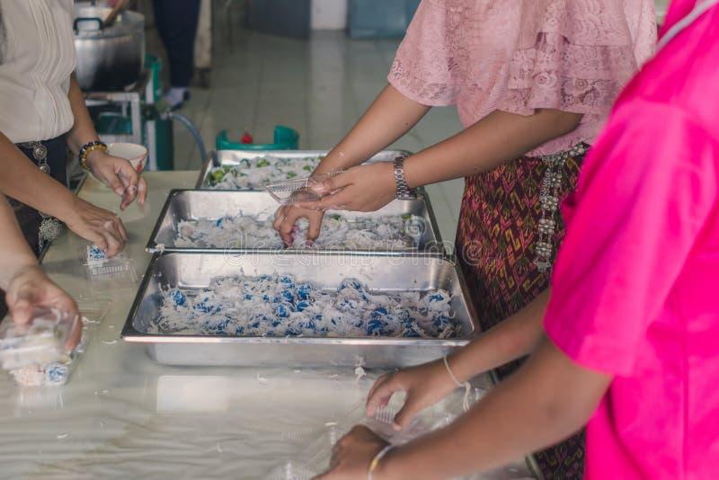 Lärare och studenter hjälper till att packa thailändsk kokosnötmunchk arkivbild