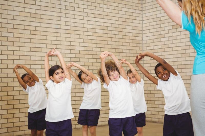 Lärare och studenter som gör elasticiteter fotografering för bildbyråer