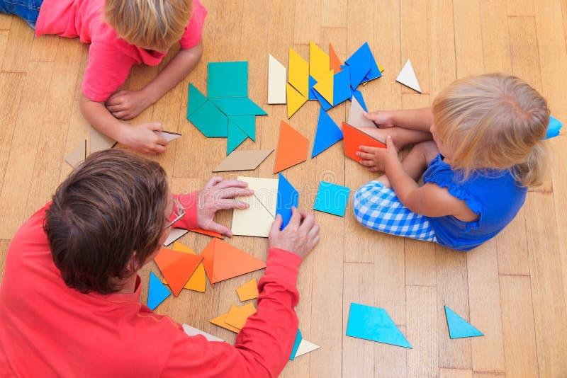 Lärare och ungar som spelar med geometriska former royaltyfria foton