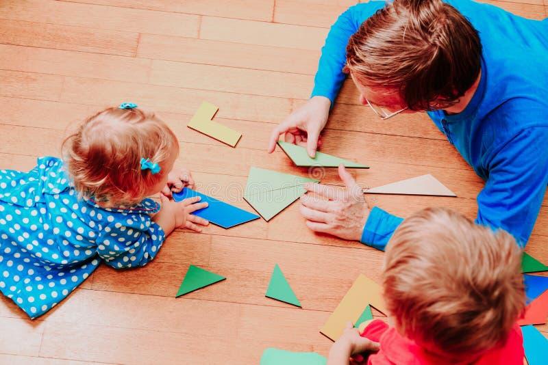 Lärare och ungar som spelar med geometriska former arkivbilder