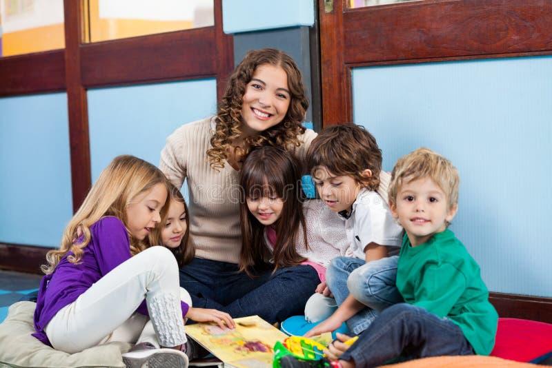 Lärare Sitting With Children på golv royaltyfria foton