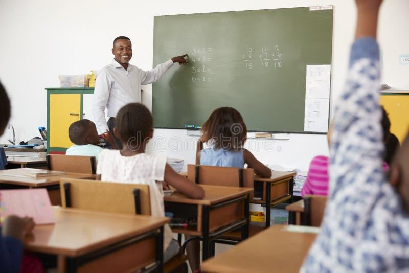 Lärare som använder den svart tavlan i en kurs på en grundskola royaltyfria bilder