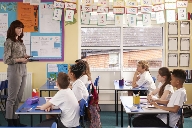 Lärare som använder minnestavladatoren under en grundskola för barn mellan 5 och 11 årgrupp royaltyfria bilder