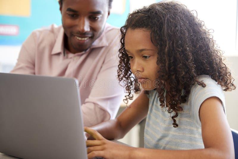 Lärare som arbetar med grundskolaflickan på bärbara datorn fotografering för bildbyråer