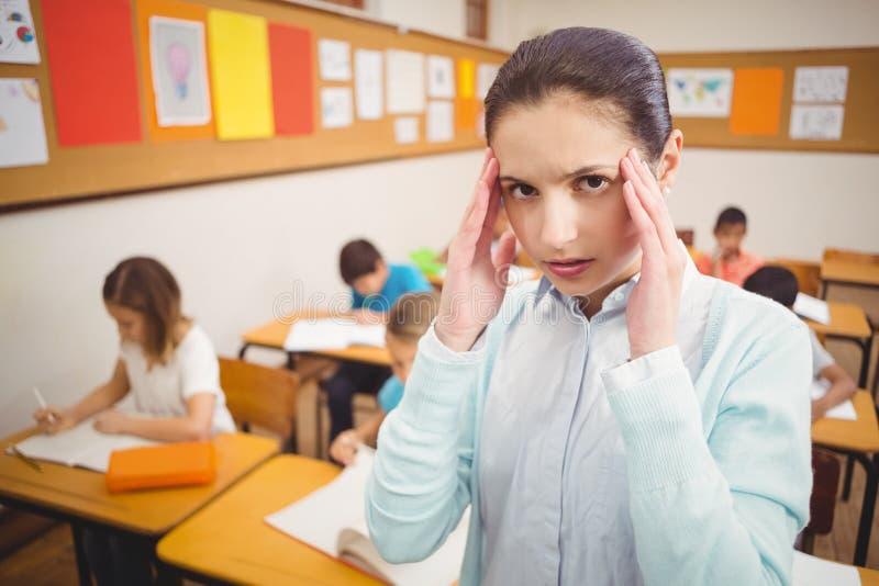 Lärare som får en huvudvärk i grupp royaltyfria bilder