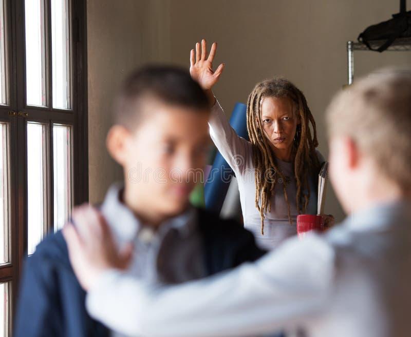 Lärare som försöker att stoppa en kamp i skola arkivbild