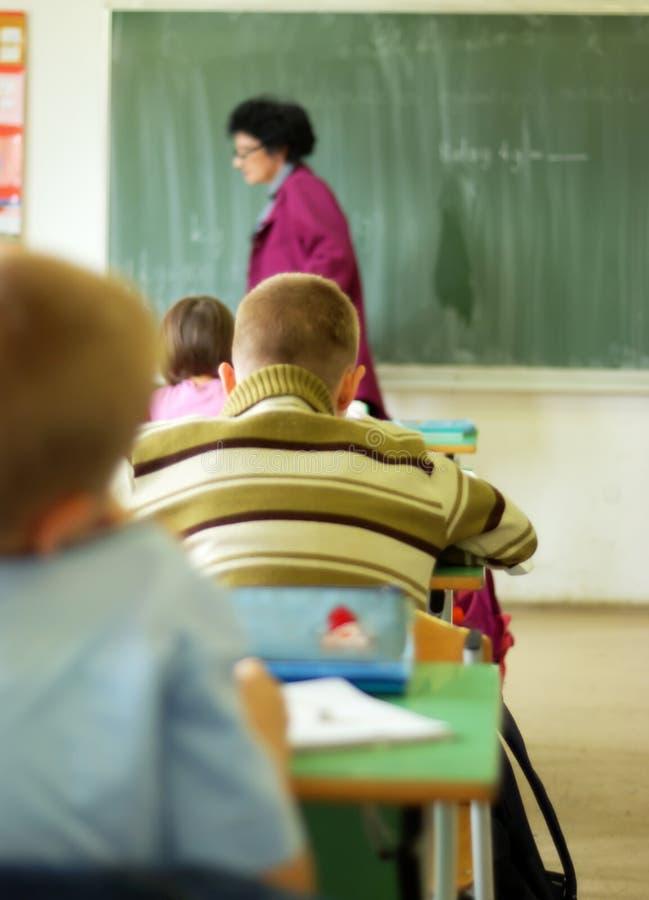 Lärare som går i klassrum royaltyfria bilder