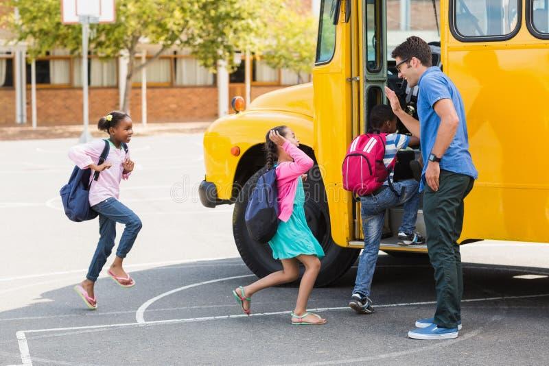 Lärare som ger höjdpunkt fem till ungar, medan skriva in i buss arkivfoto