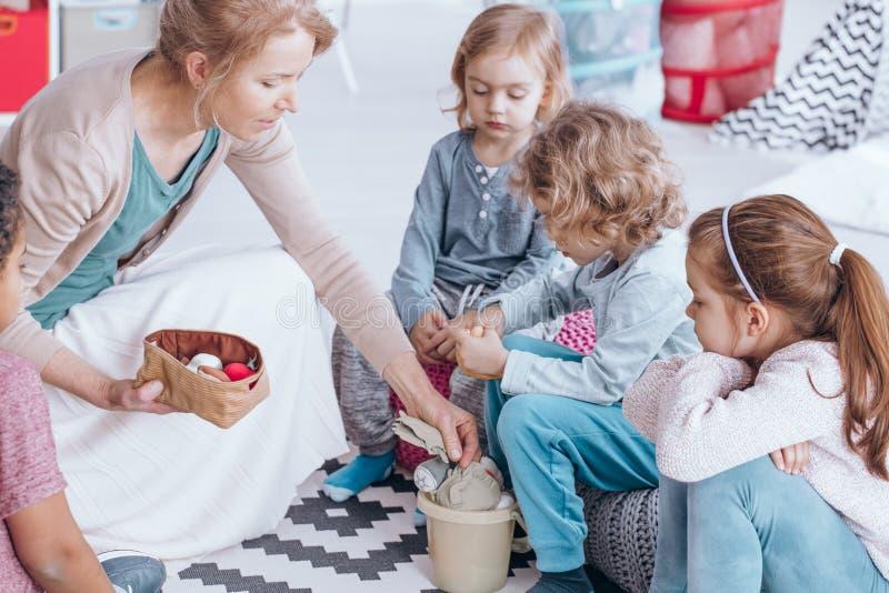 Lärare som ger leksaker till barn arkivbilder