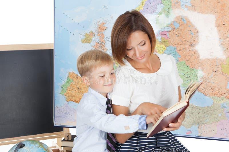 Lärare som hjälper den elementära studenten arkivfoton