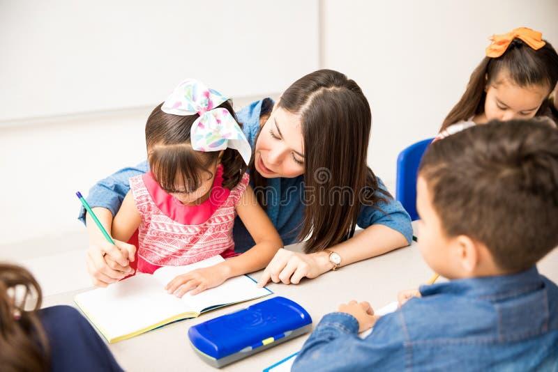 Lärare som hjälper en student med handstil royaltyfria bilder