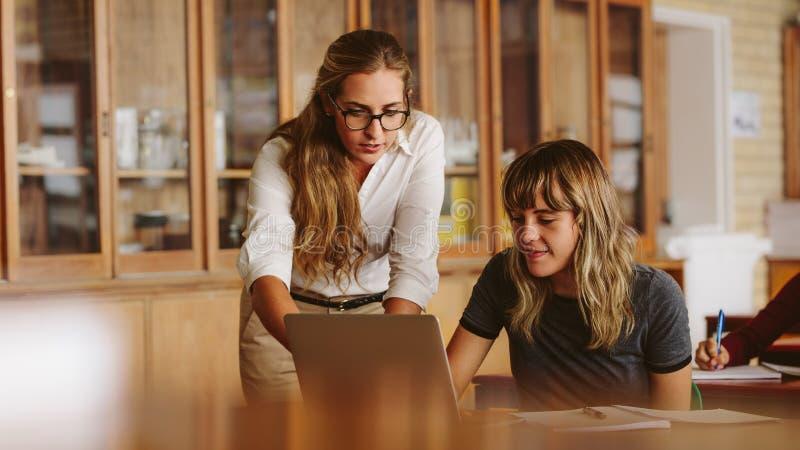Lärare som hjälper problemet av en student arkivfoton