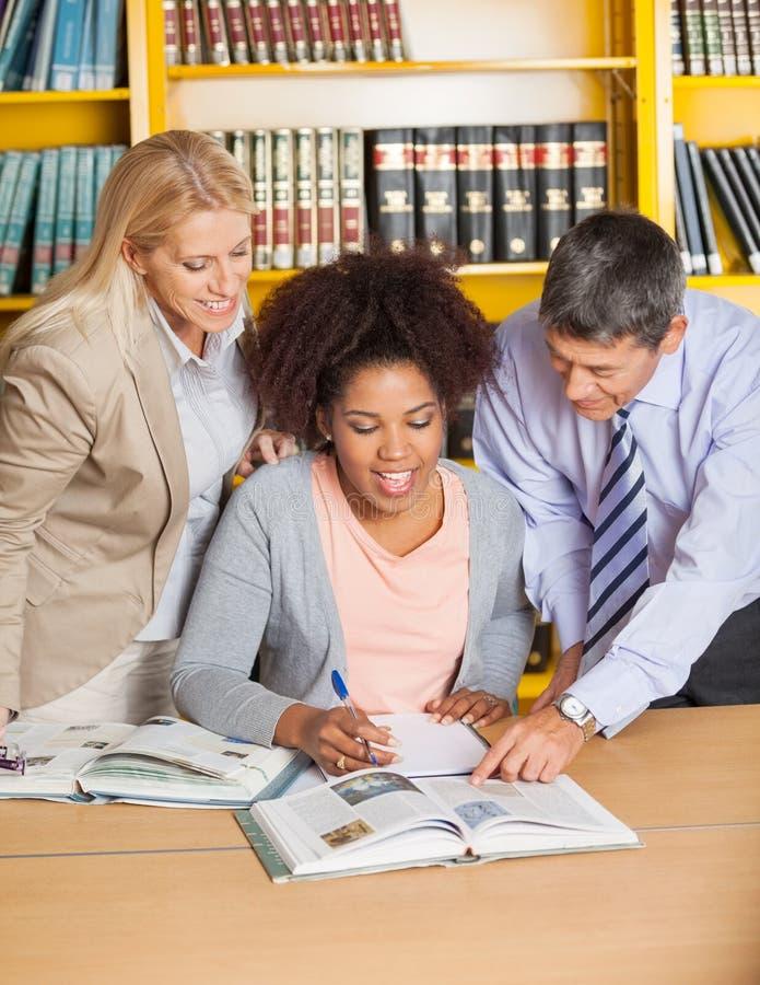 Lärare som hjälper studenten In College Library royaltyfri foto