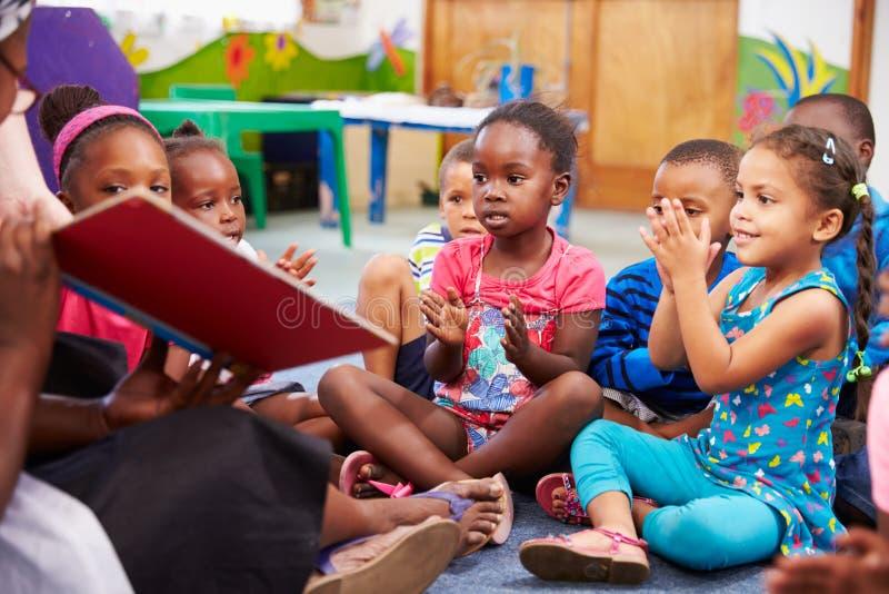 Lärare som läser en bok med en grupp av förskole- barn arkivbild