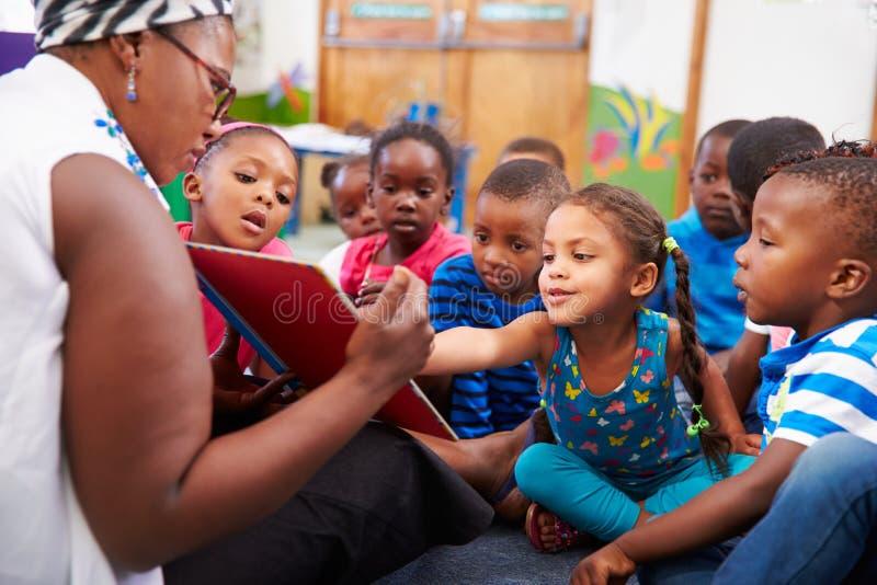 Lärare som läser en bok med en grupp av förskole- barn arkivfoto