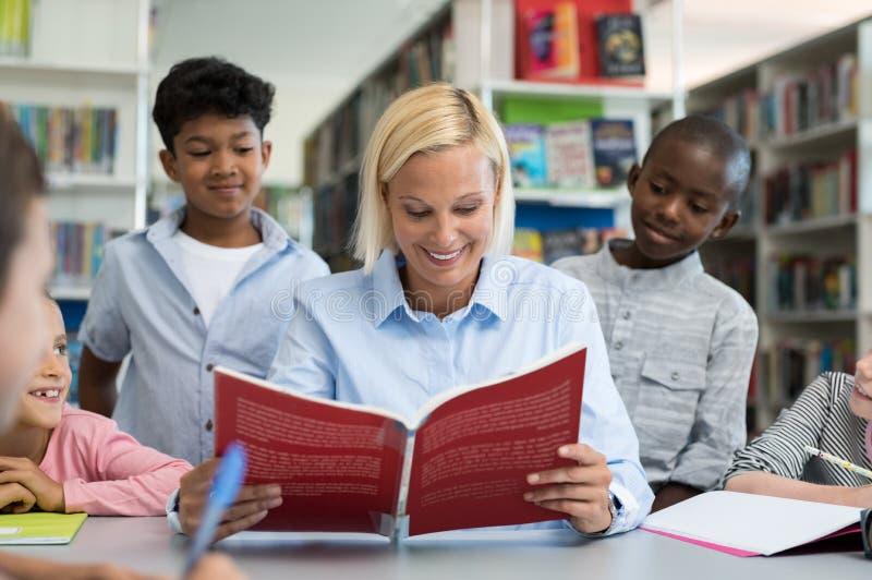 Lärare som läser en bok till barn arkivfoto