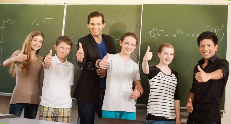 Lärare som motiverar studenter i skolagrupp arkivfoto