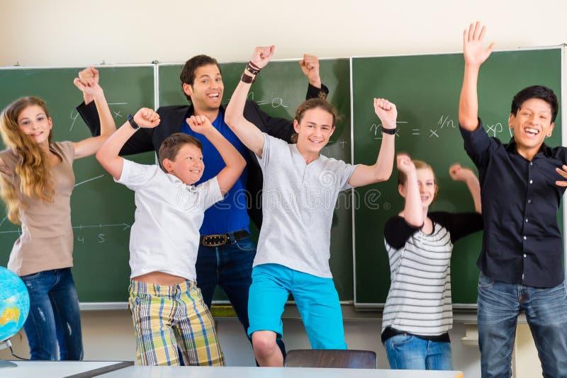 Lärare som motiverar studenter i skolagrupp arkivbild