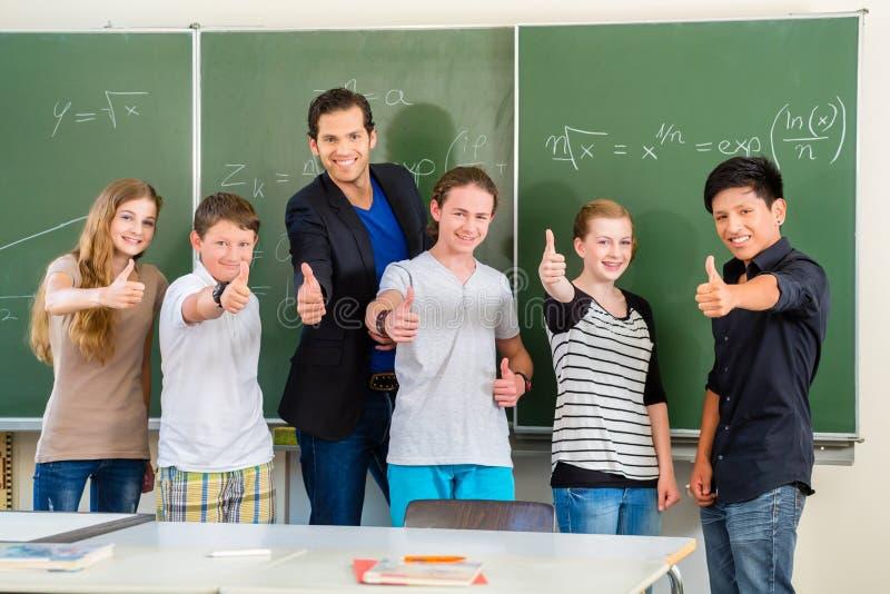 Lärare som motiverar studenter i skolagrupp royaltyfria bilder