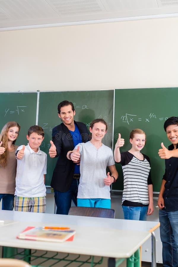 Lärare som motiverar studenter i skolagrupp fotografering för bildbyråer