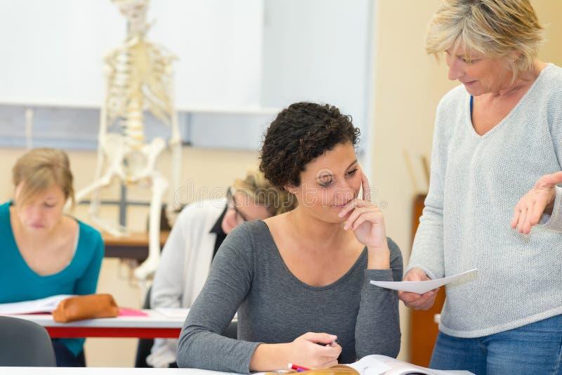 Lärare som rymmer papper och ifrågasätter studenten i anatomigrupp royaltyfria bilder