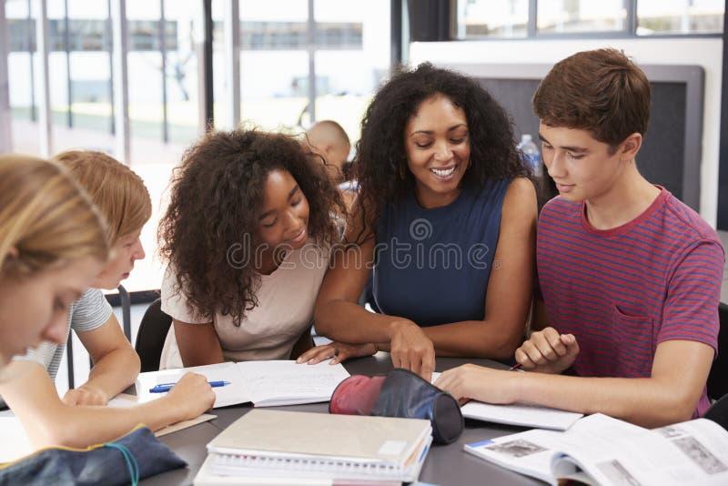 Lärare som studerar skolböcker i grupp med högstadiumungar fotografering för bildbyråer