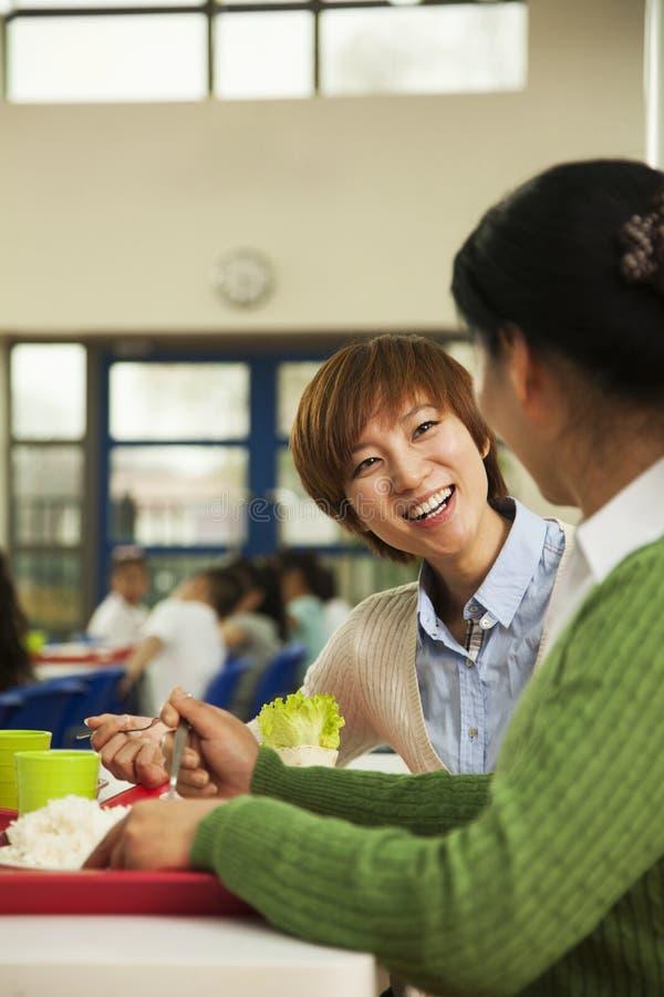 Lärare som talar på lunch i skolakafeteria royaltyfri fotografi