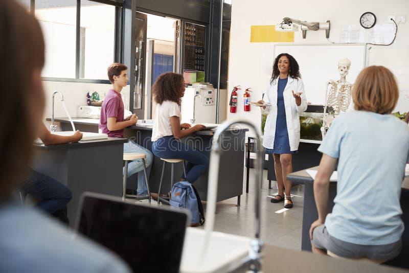 Lärare som tilltalar elever i en högstadiumvetenskapskurs royaltyfri foto