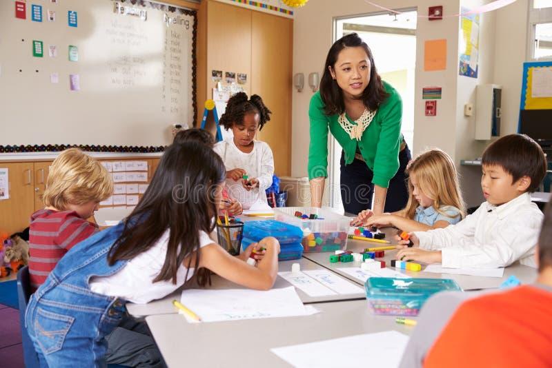 Lärare som undervisar elementära ungar med kvarterlek i grupp royaltyfri bild
