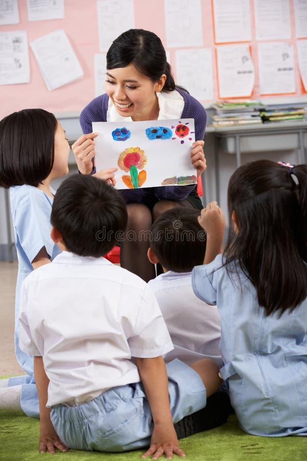 Lärare som visar målningen till deltagare royaltyfria foton