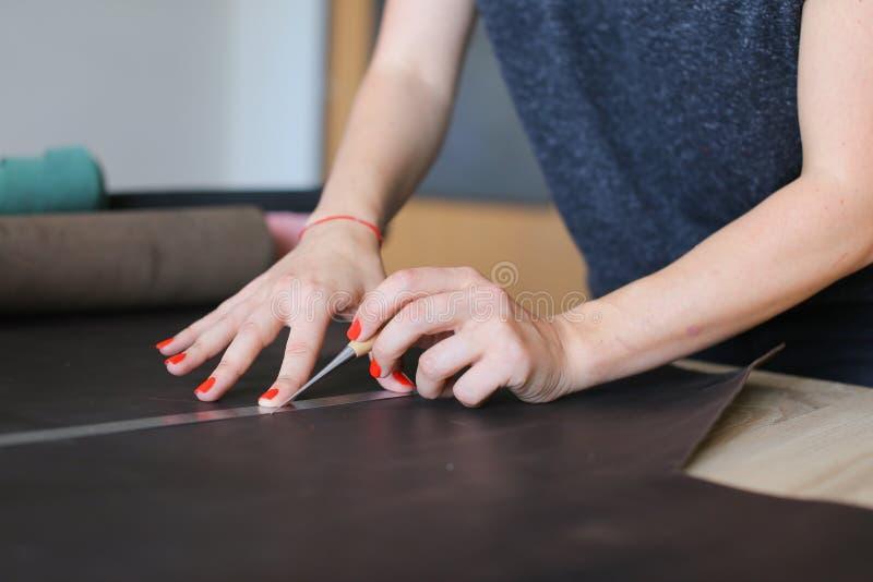 Lärare som visar studenter hur man arbetar med läder arkivfoto
