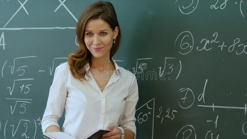 Lärare Standing In Front Of Class Asking Question och le arkivbilder