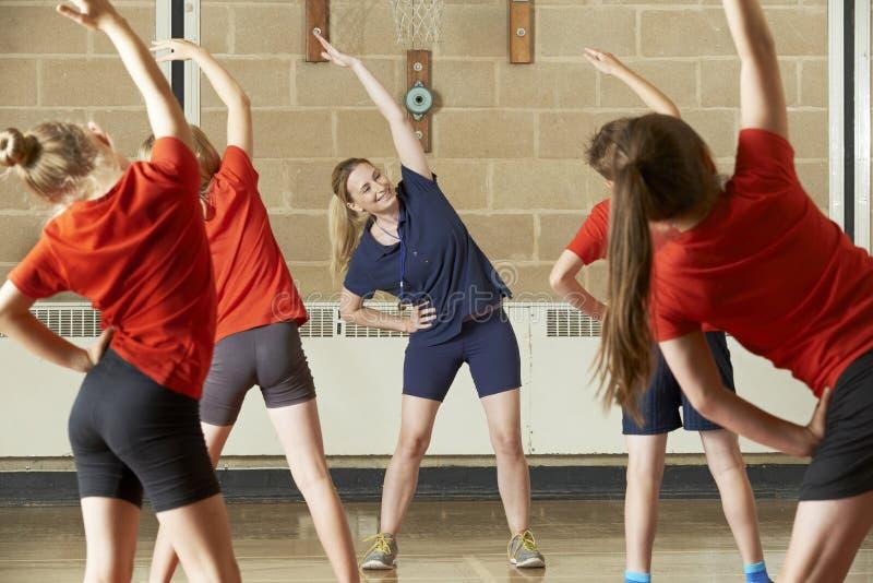Lärare Taking Exercise Class i skolaidrottshall royaltyfri foto