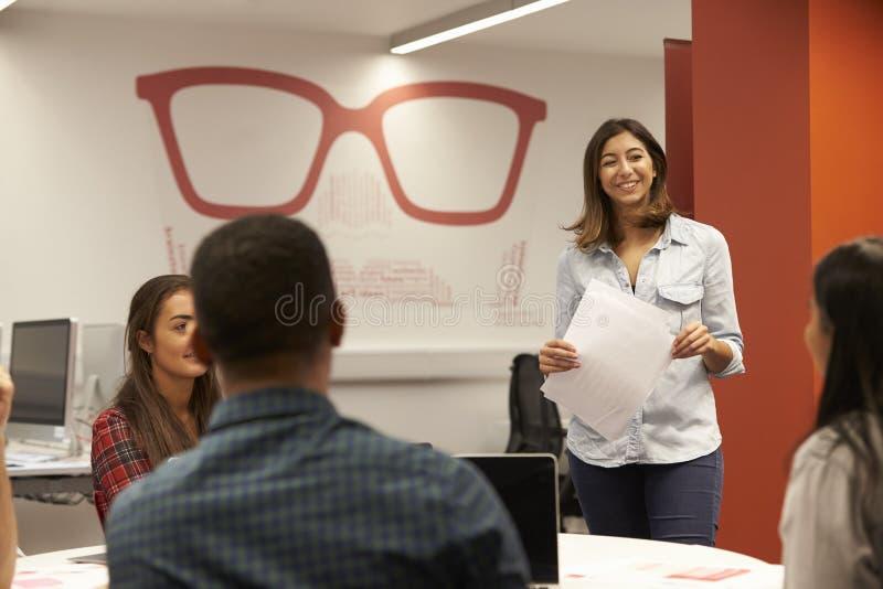 Lärare Talking To Students i högskolagrupp arkivfoto