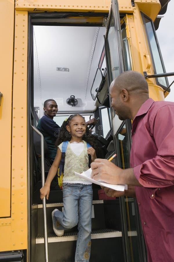 Lärare Unloading Elementary Student från skolbussen royaltyfri fotografi