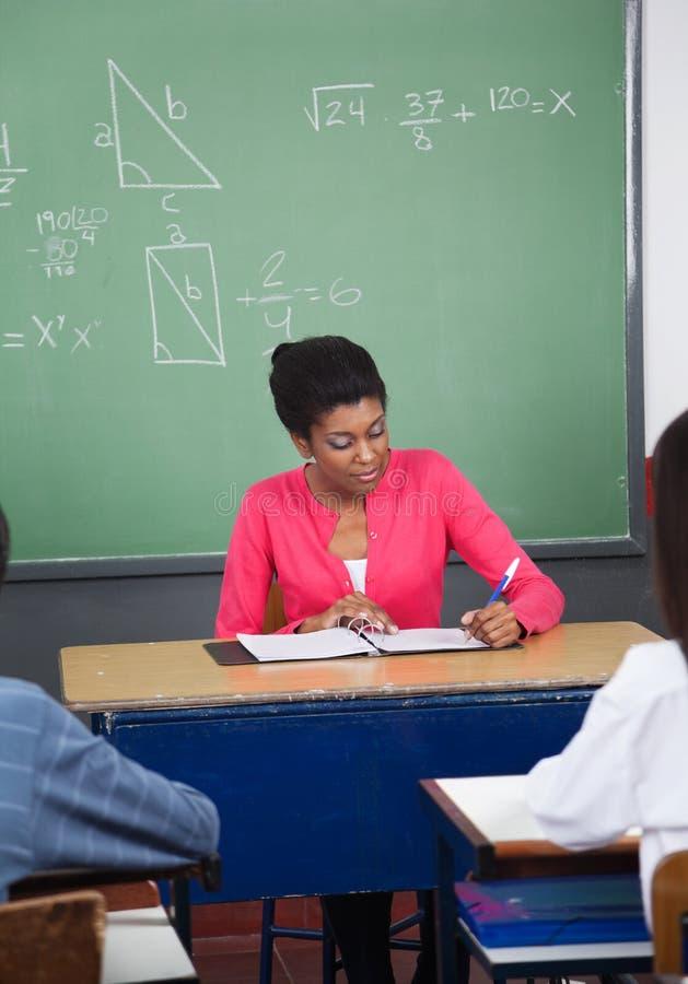 Lärare Writing In Binder på skrivbordet med studenter in fotografering för bildbyråer