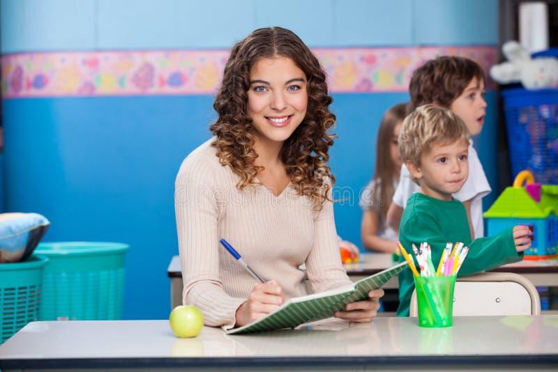 Lärare Writing In Book royaltyfria foton