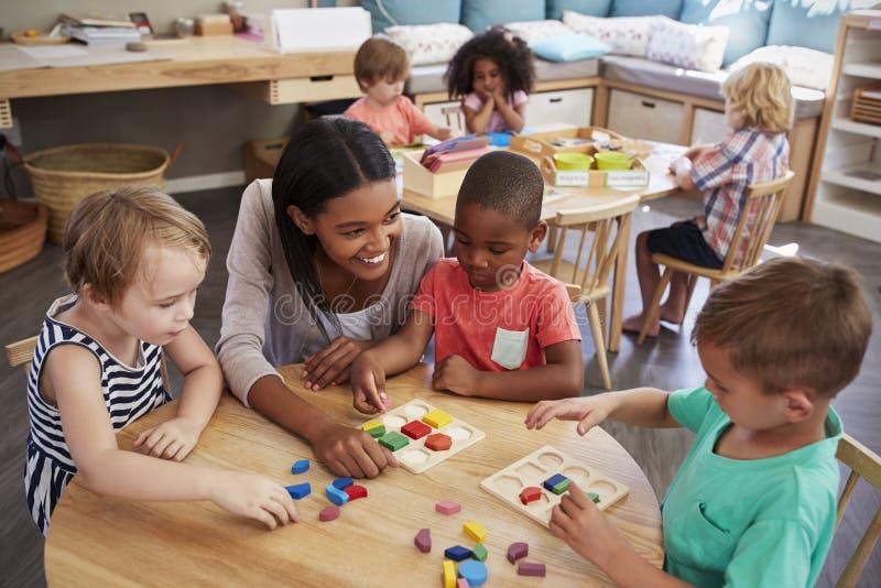 LärareAnd Pupils Using träformer i den Montessori skolan royaltyfri bild