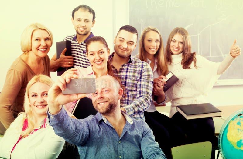 Läraredanandeselfie med studenter royaltyfri bild