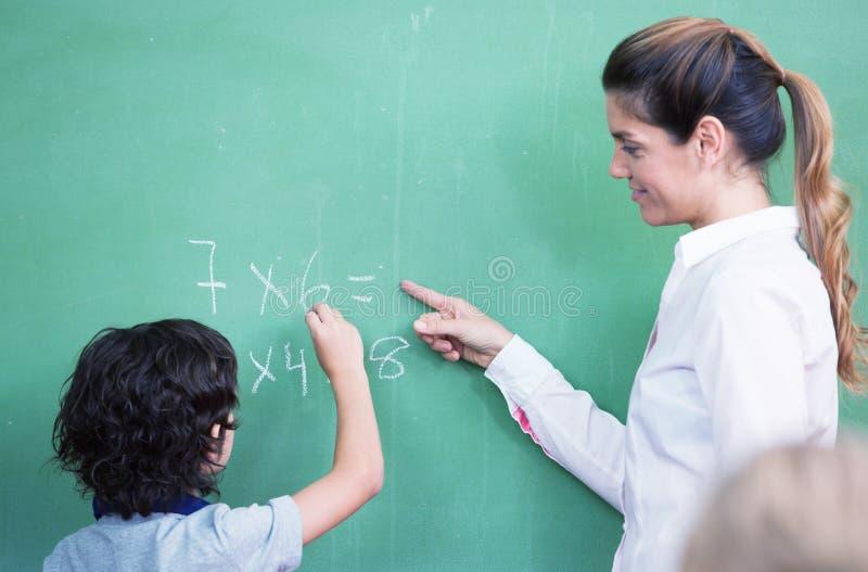 Lärareförhörunge på den svart tavlan royaltyfri bild