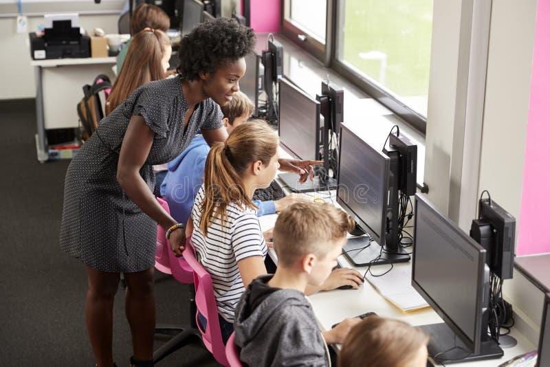LärareHelping Female Pupil linje av högstadiumstudenter som arbetar på skärmar i datorgrupp fotografering för bildbyråer