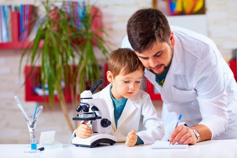 Lärarehjälpunge som för experiment med mikroskopet royaltyfri foto