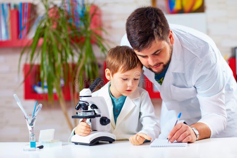 Lärarehjälpunge som för experiment med mikroskopet arkivbild