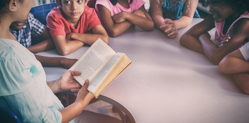 Lärareläsebok på barnblicken på henne arkivfoton