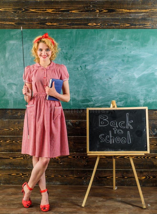 Lärareleende med boken och pekaren i klassrum Lycklig lärare tillbaka till skolan över svart tavlabakgrund Nätt och arkivbilder