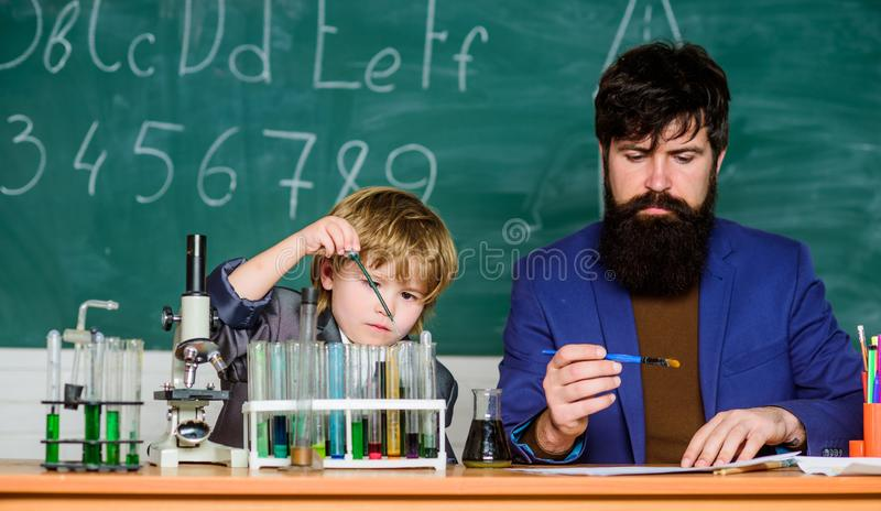 Lärareman med pysen skolalabbutrustning tillbaka skola till fader och son på skola använda mikroskopet i labb royaltyfria bilder