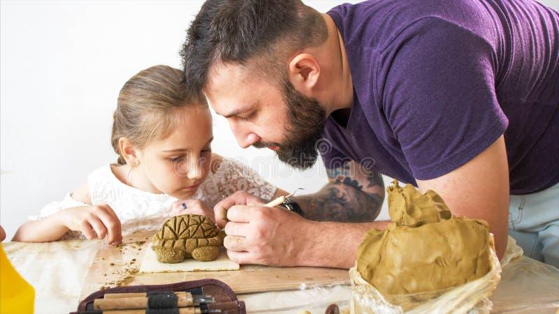 Läraren förklarar och visar hans elevflicka hur till att modellera en leksak från lera royaltyfri bild