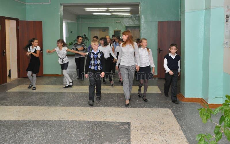 Läraren går med barnen längs skolakorridoren arkivbild