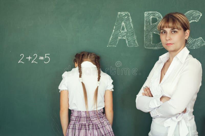 Läraren har bestraffat skolflickan för det fel exemplet royaltyfria foton