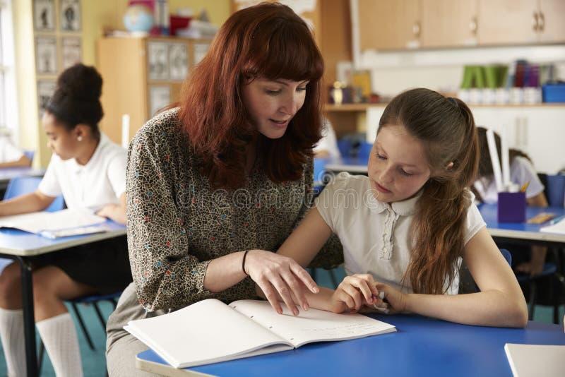 Läraren hjälper en flicka på hennes skrivbord, slut upp båda som ner ser arkivbild